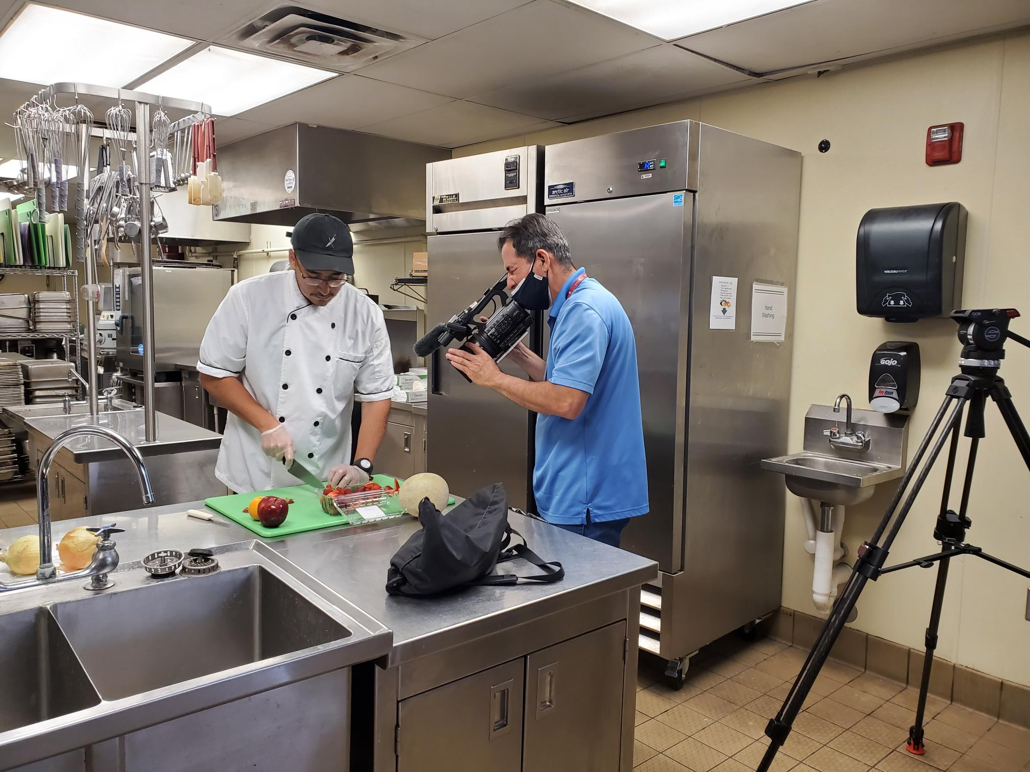 Art Ruiloba, right, films Gilbert Morales, a New Mexico State University alumnus who graduated from the School of Hotel, Restaurant and Tourism Management, cutting fruit for a new promotional video for the HRTM program. (Courtesy)
